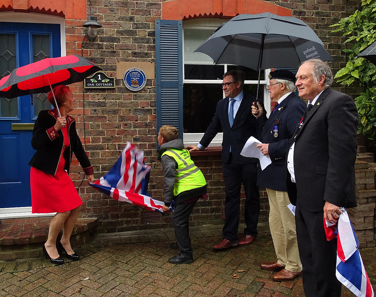 Unveiling plaque at 1 Sandy Lane with assistance from schoolboy.